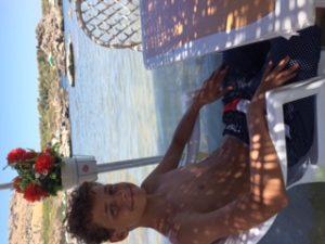 Sønnike med fødder i vand, imens frokosten nydes på Nikolas Beach, Rhodos